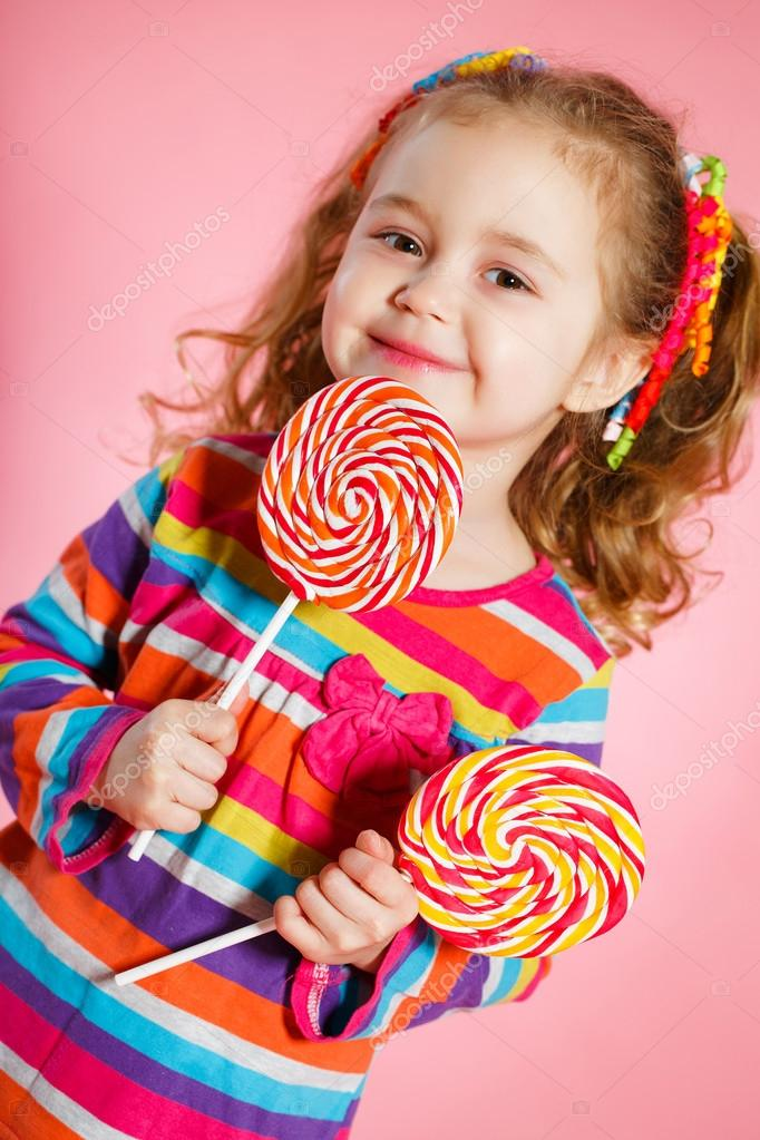 1831cc461 Funny little girl with long, curly red hair,bright ribbons tied into two  tails, a sweet smile,wearing a bright dress with a red bow on the  chest,posing in ...