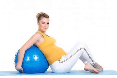 A pregnant woman does gymnastics with ball
