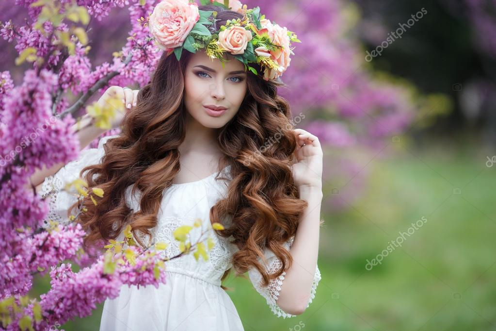 Spring portrait of a beautiful woman in a wreath of flowers