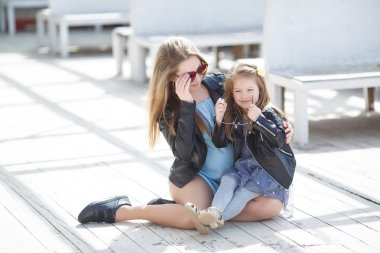 Fashionably dressed mother and daughter on the street in the spring