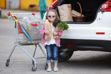 Girl with a shopping cart full of groceries near the car