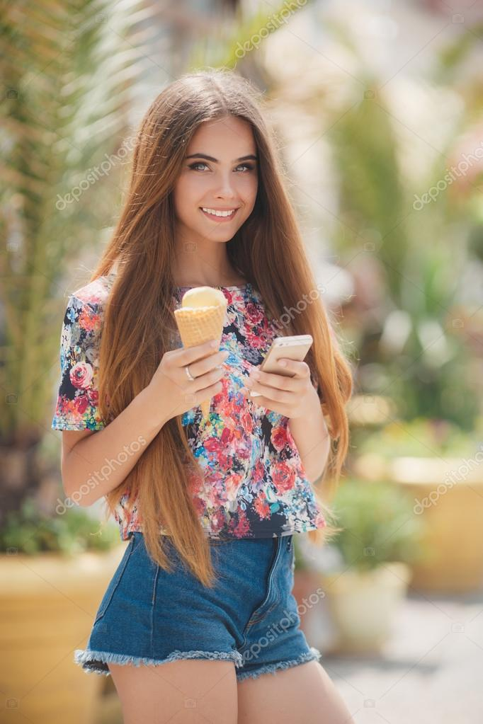 Beautiful Girl With Ice Cream Reads Message On Mobile Phone  Stock Photo  Golyak -1963