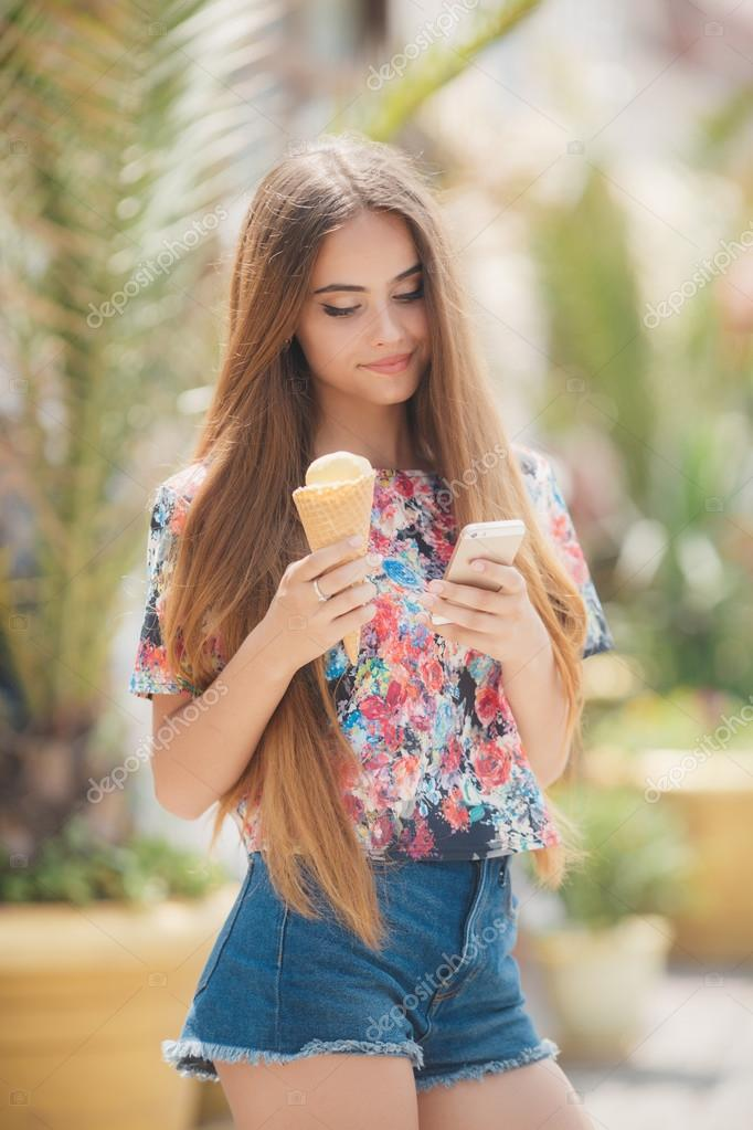 Beautiful girl with ice cream reads message on mobile phone– stock image