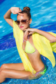 A slender girl with yellow pareo by the pool