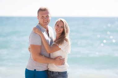 Young loving couple on the beach near the sea