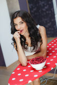 Photo Young woman smiling eating fruit salad raspberry