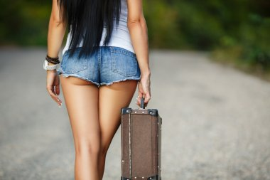 Lonely Girl with a suitcase on a country road ...