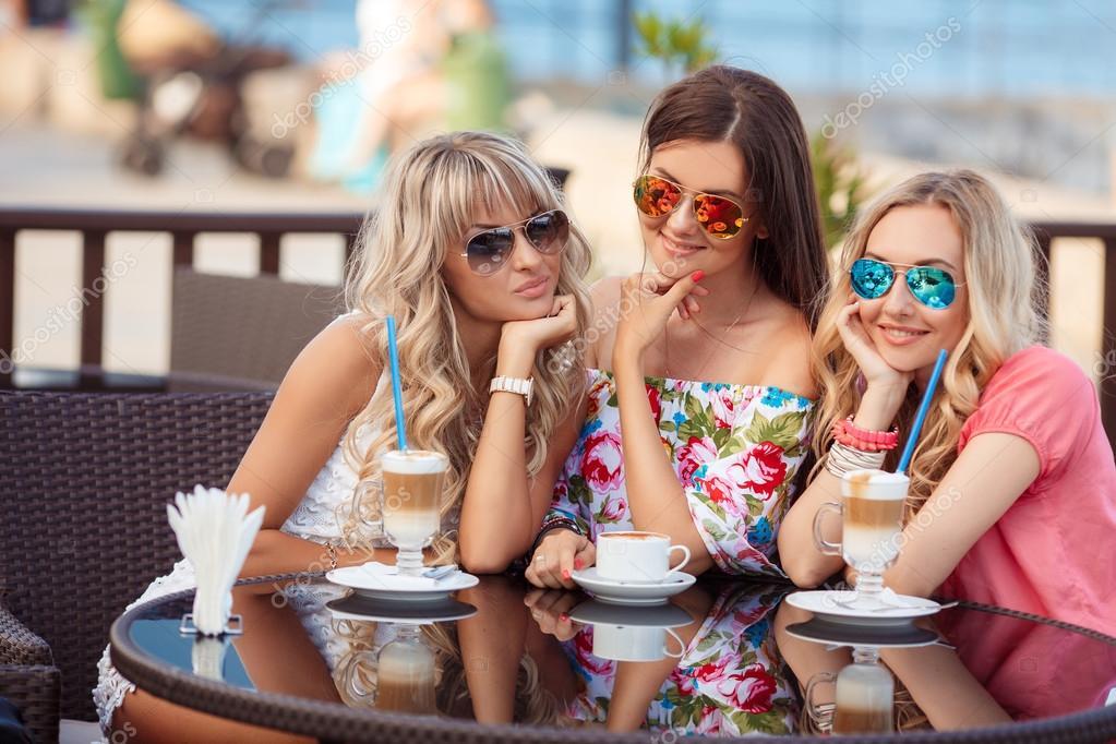 Three Women Enjoying Cup Of Coffee In Cafe.
