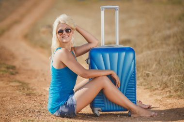 Blonde sitting on suitcases at the side of the road