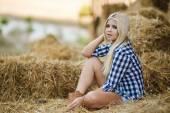 Sexy blond žena odpočívá na seno ve venkovských oblastech