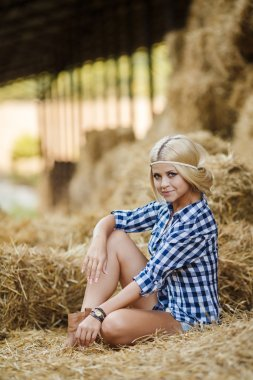 Sexy blonde woman resting on hay in rural areas