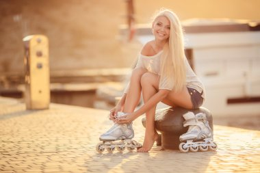 Beautiful girl on roller skates in the park.