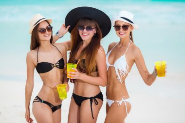 Three girls in hats drinking juice near the sea