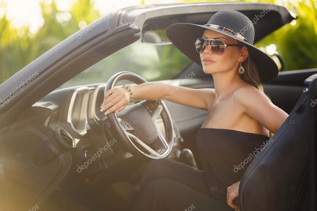portrait d 39 une jeune femme dans la voiture dans un grand chapeau noir photographie golyak. Black Bedroom Furniture Sets. Home Design Ideas