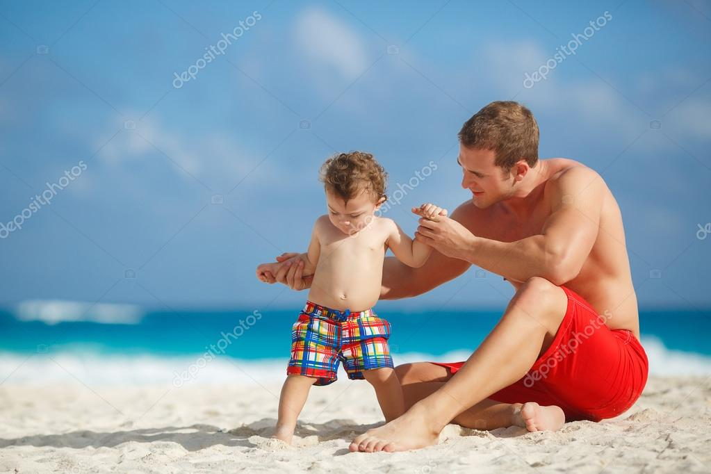 Young father with a young son play near the ocean.