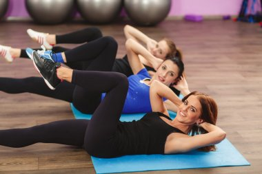 Girls perform exercises for abdominal muscles.