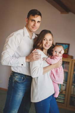 Happy young family with a small child in her arms.