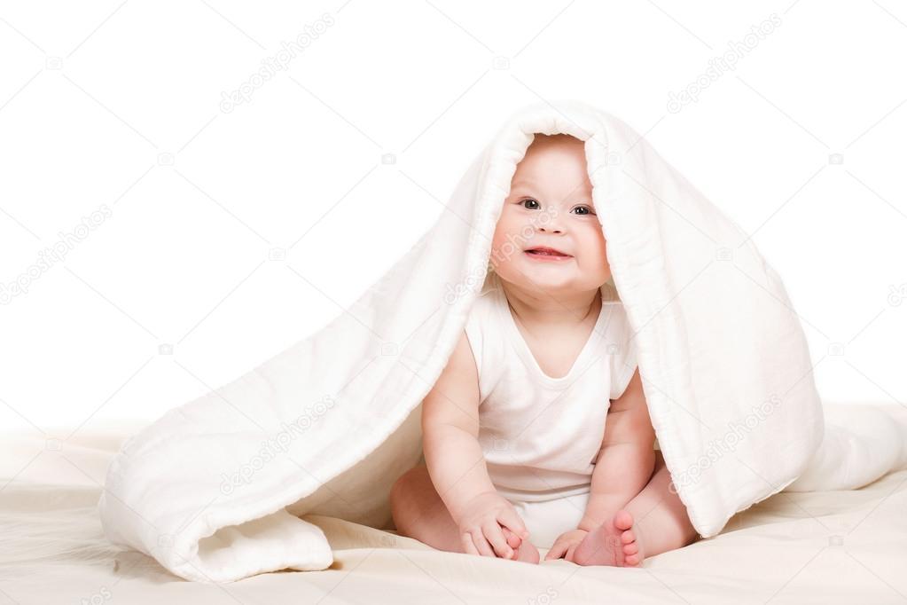 Nettes Baby spähen aus unter der Decke, spielen auf dem