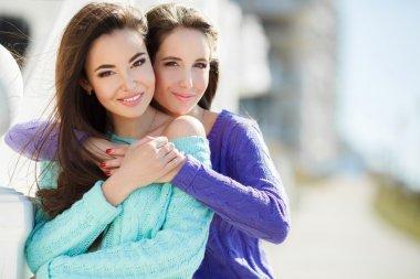 Urban portrait of two beautiful girlfriends.