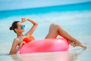 Beautiful woman with an inflatable life buoy on a tropical beach