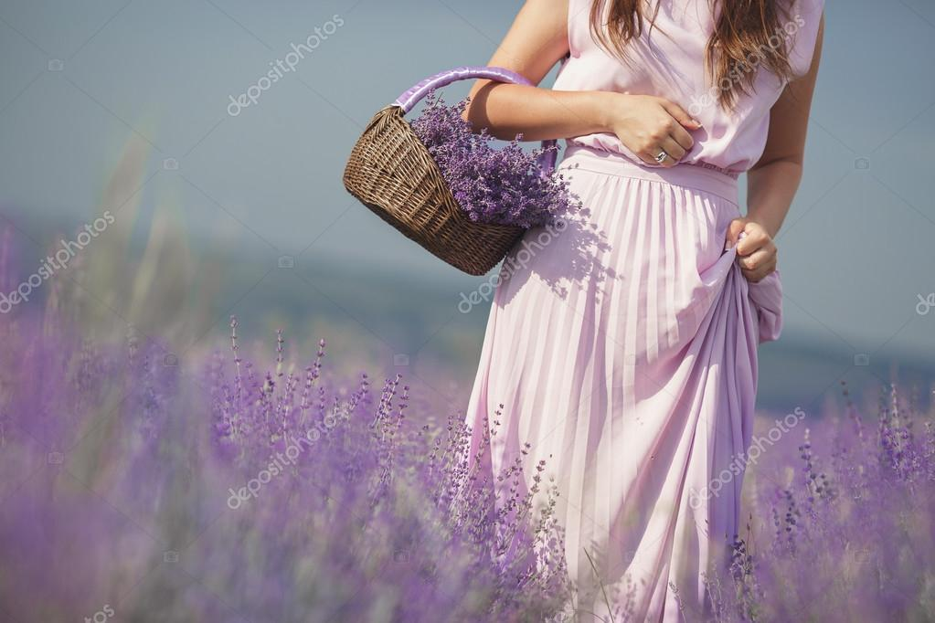 The young woman in the field of the blossoming lavender