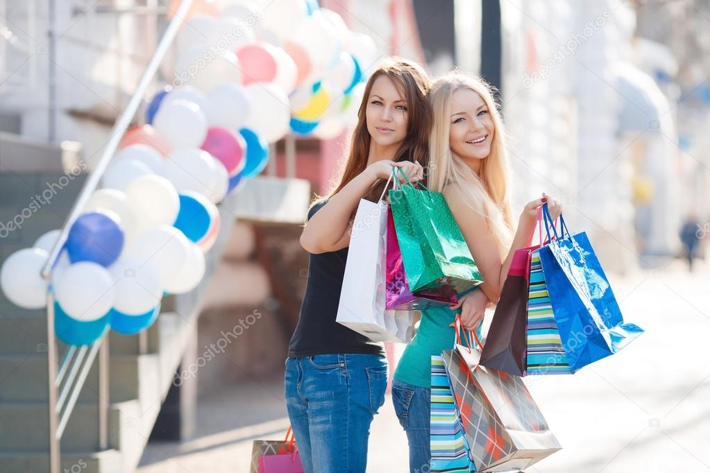 Two Beautiful Girls With Colorful Shopping Bags