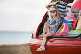 Fotografie Portrait of a little girl sitting in the trunk of a car
