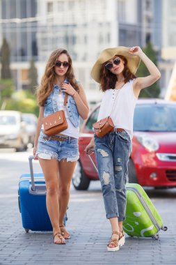 Women traveling with suitcases, walking on the road to the airport