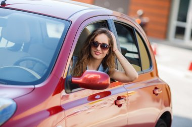 Happy young woman in car driving on the road.