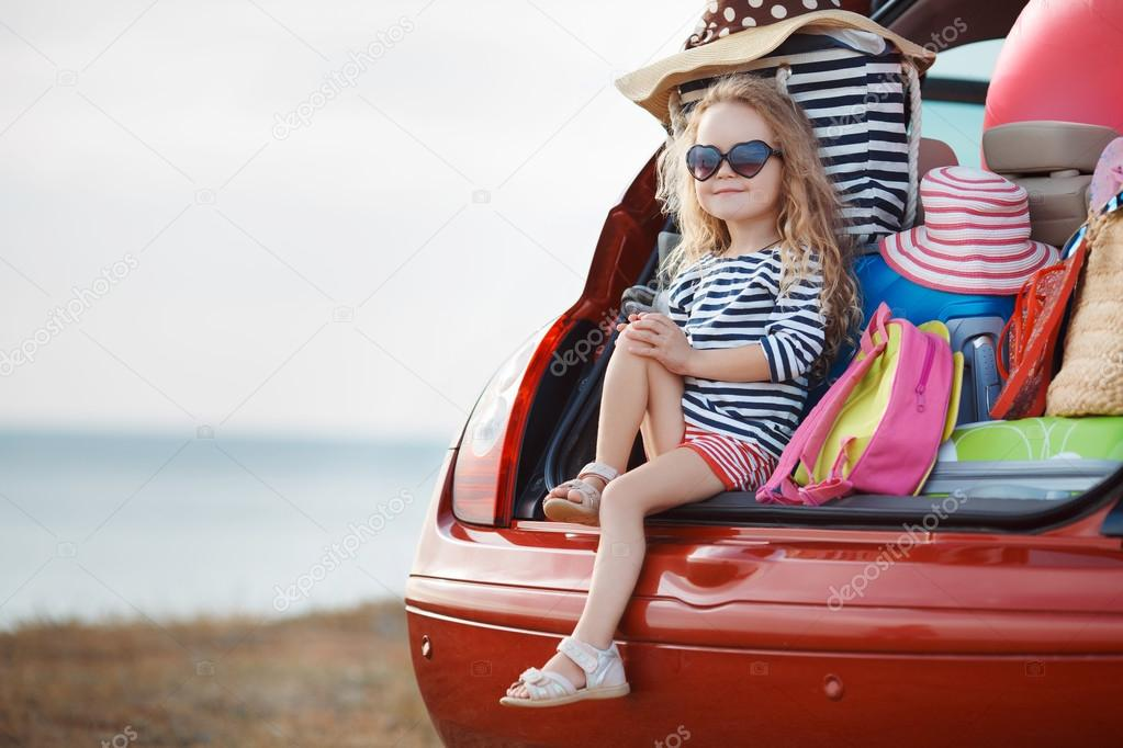 Portrait of a little girl sitting in the trunk of a car