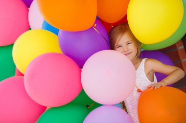 Portrait of little girl playing with air balloons.