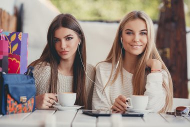 Two girls in a cafe listening to music in earphone