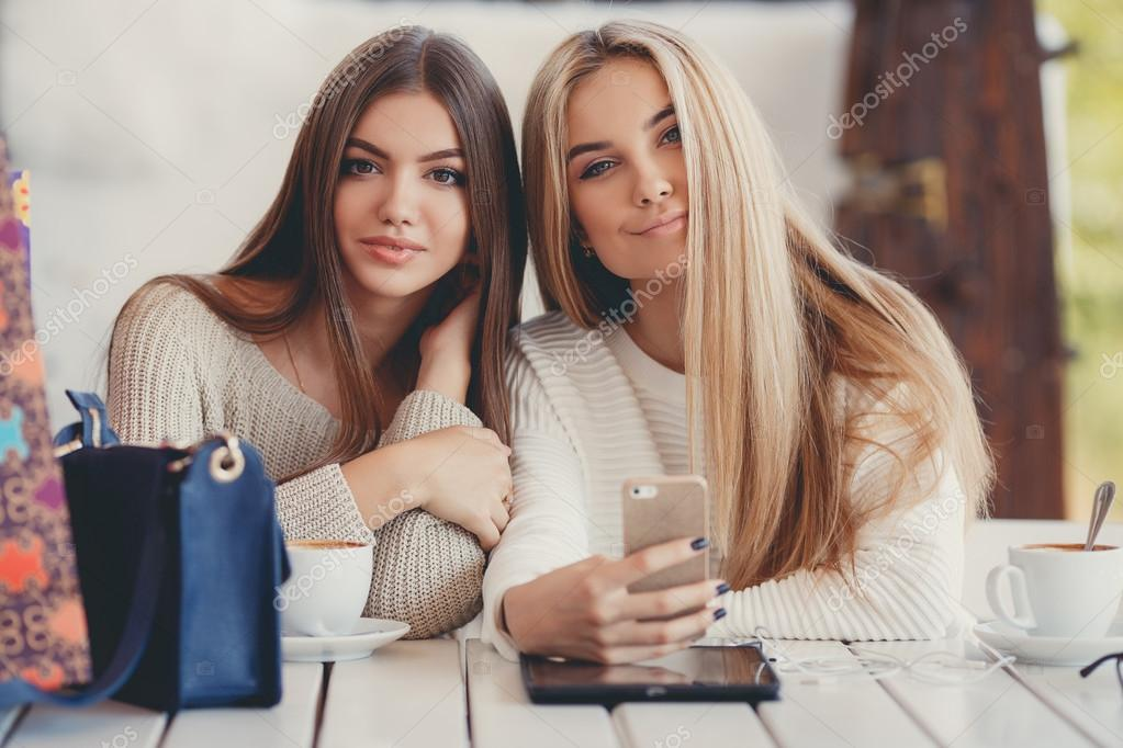 688cdb244f Two young women at cafe looking at pictures of new gadgets — Stock Photo
