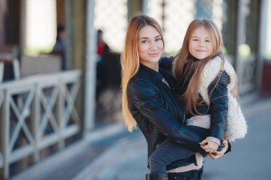 Spring portrait of a happy family,red-haired mother and daughter brunette with long straight hair,dressed in black leather jackets, spend time together,mother holds daughter on hands standing near a country house. stock vector