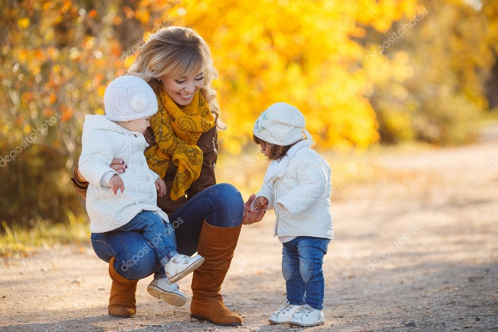 Happy mother with children in autumn park