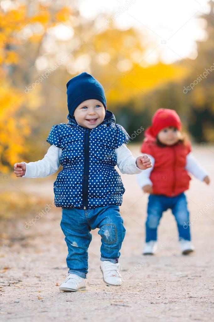 Little girls - girlfriends walk in the park.