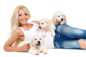 Beautiful blonde with a small white puppy of Labrador