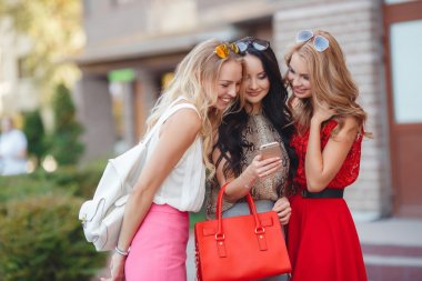 Three girlfriends looking at pictures on smartphone