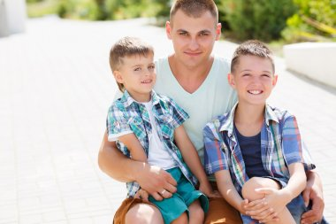 Happy young father,a brunette with short hair, spends time on the street in the summer with his two sons,boys 5-7 years old, children dressed in plaid shirts short sleeve,walk and have fun together in the yard near multi-storey buildings. stock vector