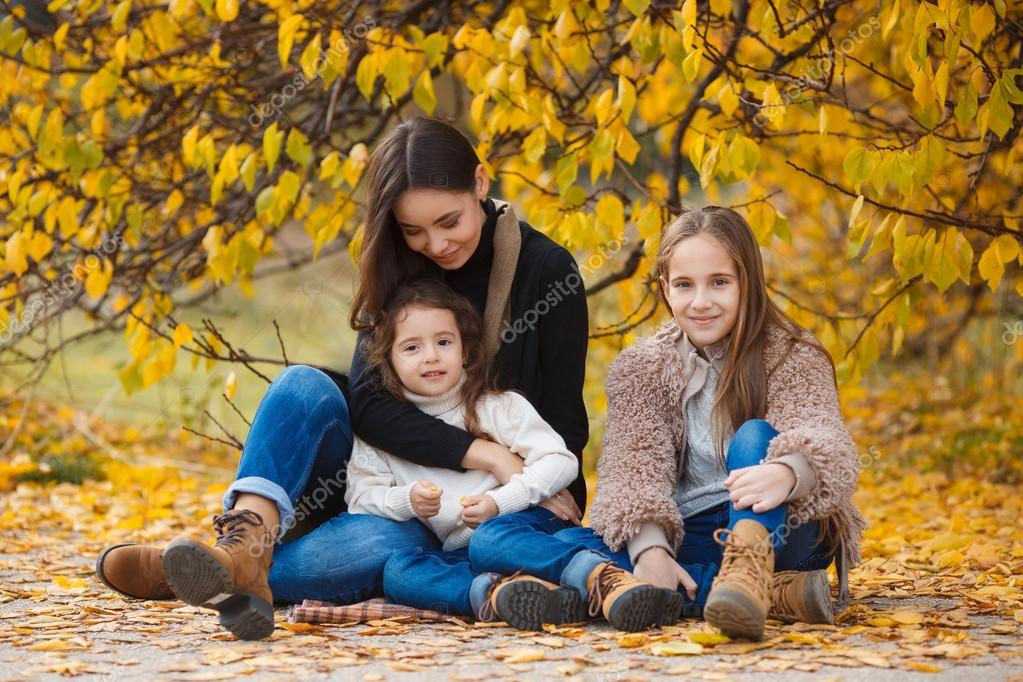 Family portrait of sisters in yellow autumn Park