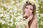 Fotografie Beautiful young woman in a field of blooming daisies