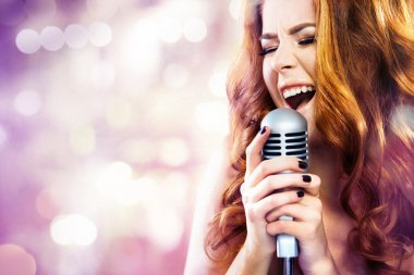 Glamor fashion Woman with Microphone over Blinking bokeh night background.