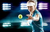 Krásná dívka tenista s raketou na tmavém pozadí se světly