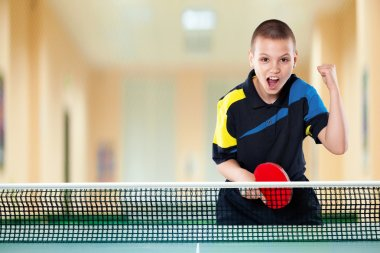 Little boy celebrating flawless victory in table tennis