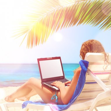 Young caucasian woman is surfing internet with the notebook at sunset beach. Laptop display is cut with clipping path stock vector