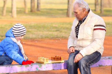Grandfather and grandson playing chess outdoors