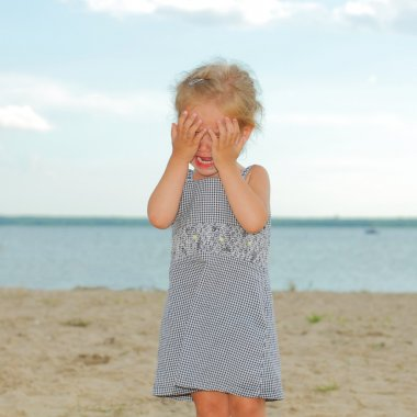 Crying little girl on the beach