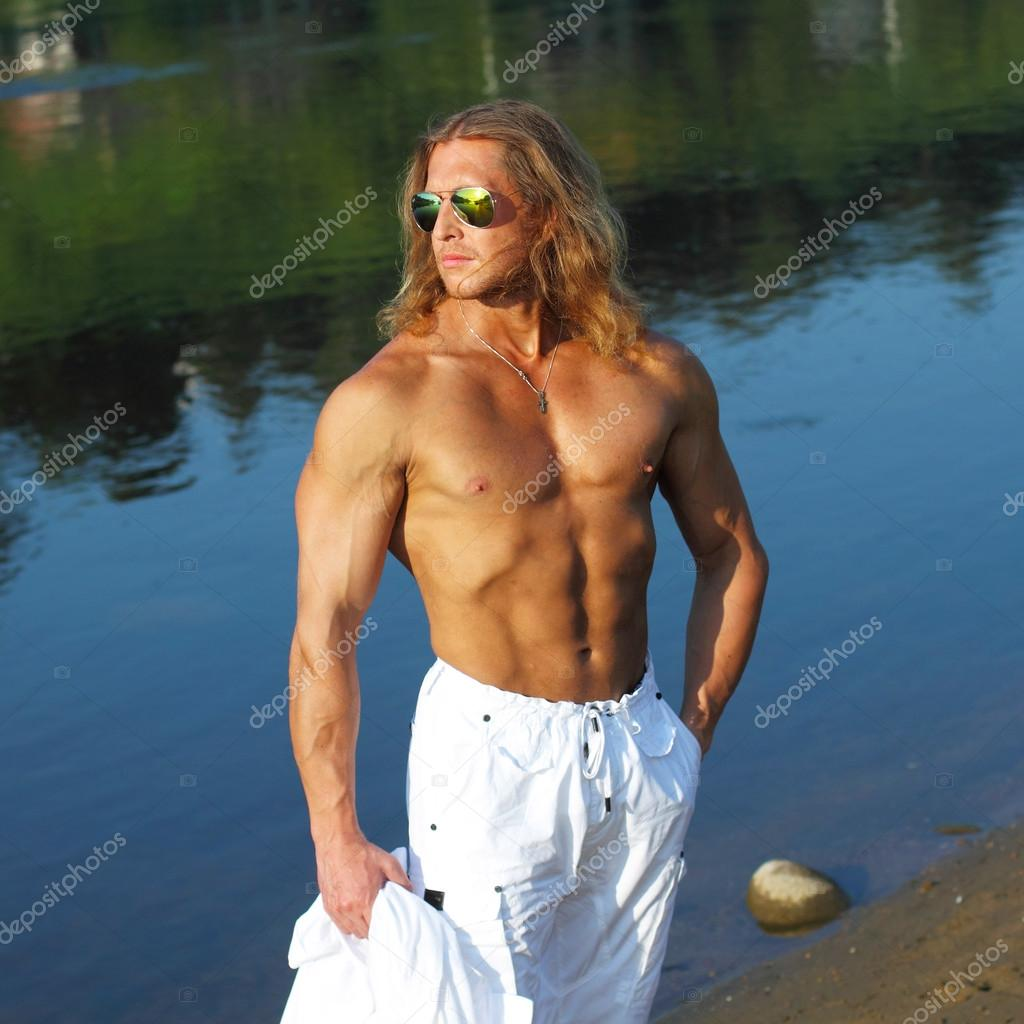 Fitness man in sunglasses on the beach