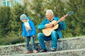 Großvater und Enkel spielen Gitarre