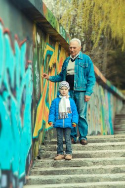 Grandfather and grandson are painting graffiti